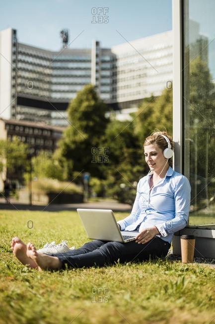 Smiling woman wearing headphones sitting on urban meadow using laptop