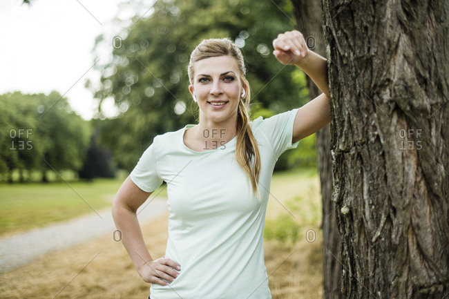 Smiling sportive young woman leaning against a tree in a park