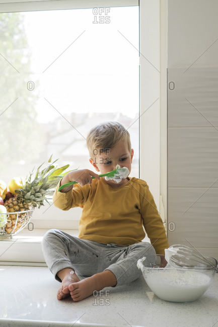 Portrait of little boy sitting barefoot n worktop in the kitchen nibbling whipped cream