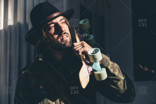 USA- New York City- portrait of bearded man with skateboard wearing black hat