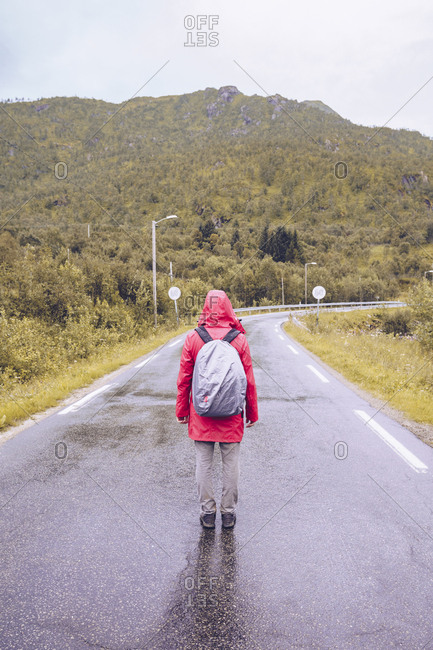 Norway- Lofoten- back view of man wearing red rain jacket and backpack standing on wet road
