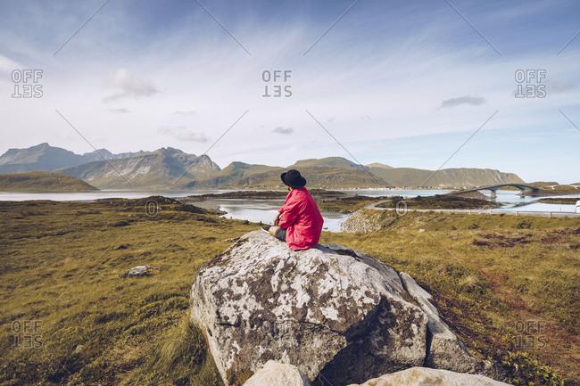 Norway- Lofoten- man wearing red rain jacket sitting on a rock looking at view