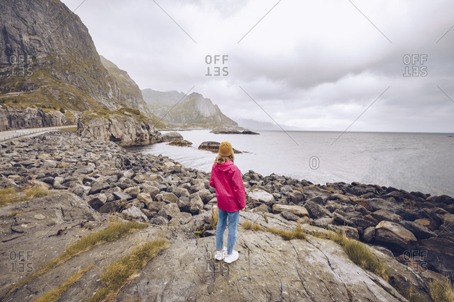 Norway- Lofoten- back view of young woman wearing rain jacket standing on a rock looking at distance