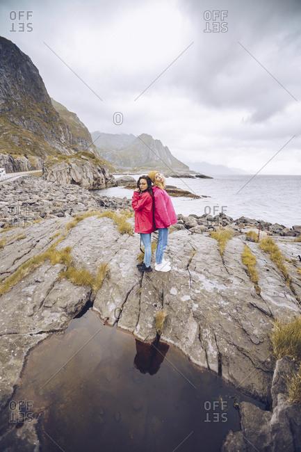 Norway- Lofoten- two women wearing rain jackets standing back to back on a rock