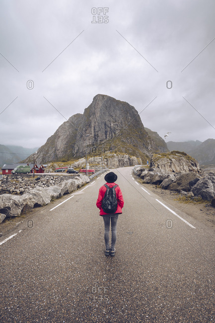 Norway- Lofoten- Hamnoy- back view of man with backpack standing on empty road