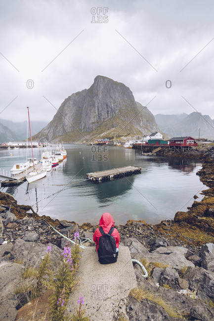 Norway- Lofoten- Hamnoy- back view of man wearing red rain jacket and backpack looking at view