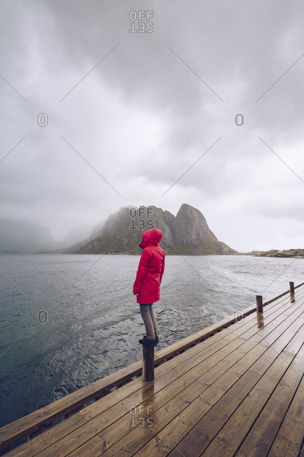 Norway- Lofoten- Hamnoy- man wearing red rain jacket standing on wooden stake looking at distance