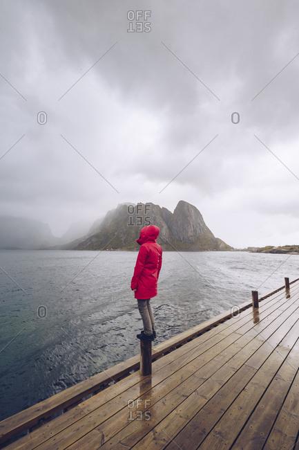 Norway- Lofoten- Hamnoy- man wearing red rain jacket standing on wooden stake looking at distance