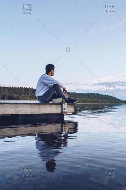 Young man sitting at lake Inari- looking at view- Finland