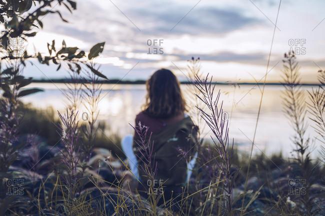 Young woman sitting at lake Inari- looking at view- Finland