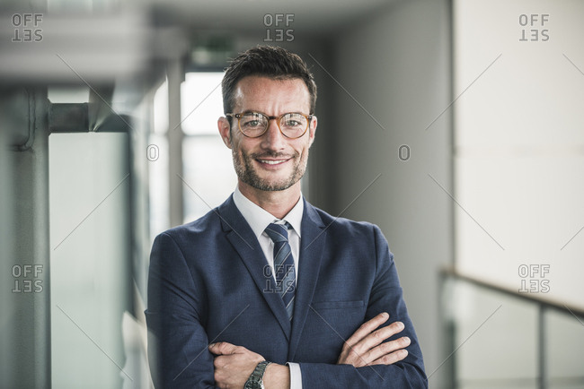 Portrait of a successful businessman- standing in office building- with arms crossed