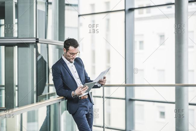 Businessman standing in office building- using digital tablet