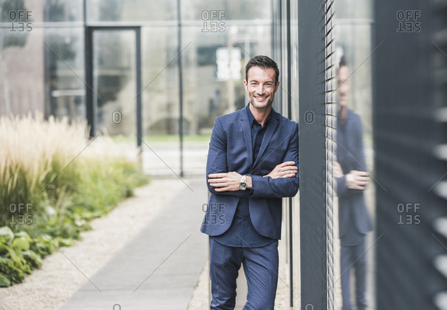 Portrait of a businessman leaning on a wall- smiling