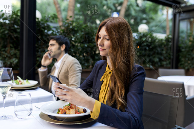 Man and woman using cell phones in a restaurant