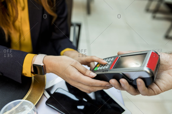 Woman entering pin into card reader in a restaurant