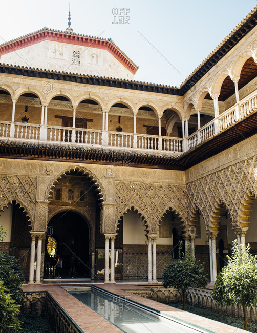 El Alcazar, Seville, Spain - October 6, 2016: Interior courtyard with foliage and ornate Islamic arches and fountain
