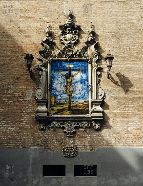 Seville, Spain - October 7, 2016: Tile artwork of Jesus with decoration on wall