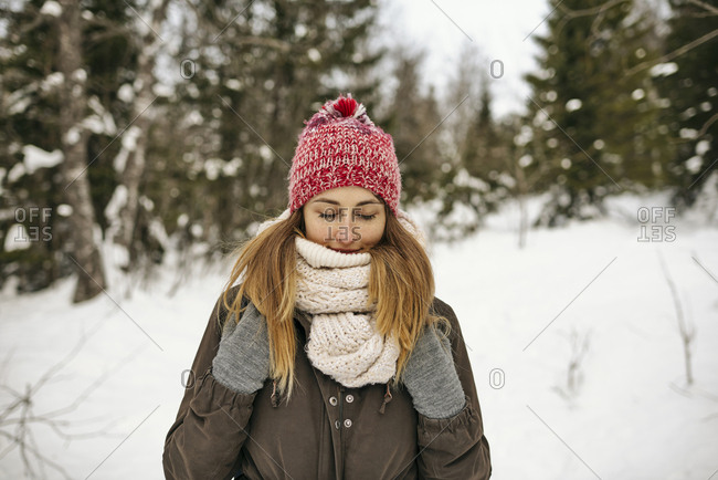 Woman in warm outwear standing with backpack in snowy woods keeping eyes closed and dreaming in daylight