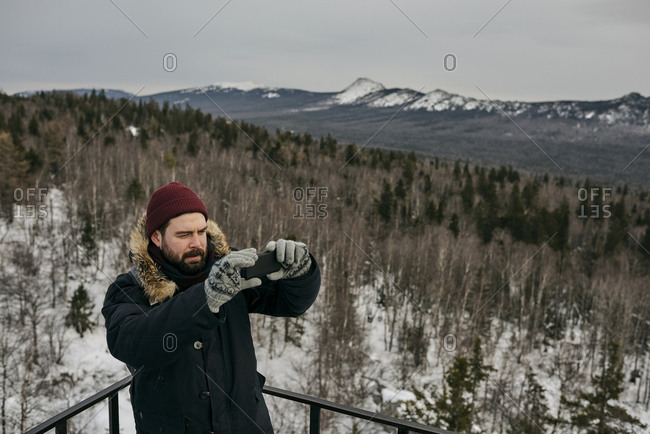 Traveling man in warm outwear and hat using phone and taking photo of landscape from high point in winter time