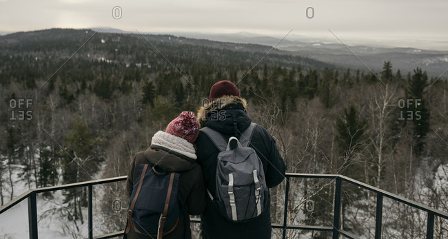 Back view of man and woman with backpacks standing close on viewpoint against highlands