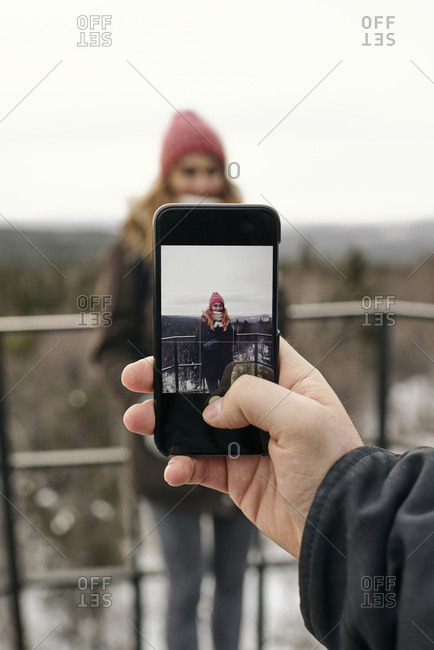 Crop male hand using smartphone and photographing smiling girlfriend on terrace against highlands