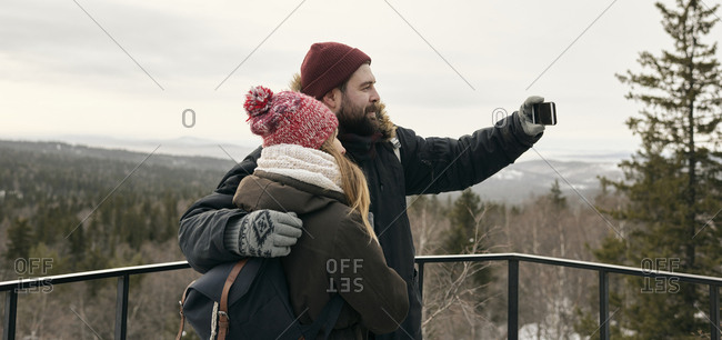 Side view of man and woman in outwear standing with backpacks and taking selfie in highlands on viewpoint