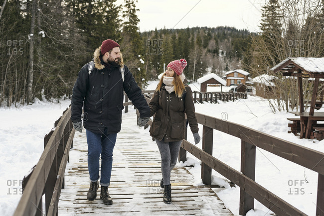 Amorous couple in outwear backpacking together and walking on wooden pathway in snowy nature