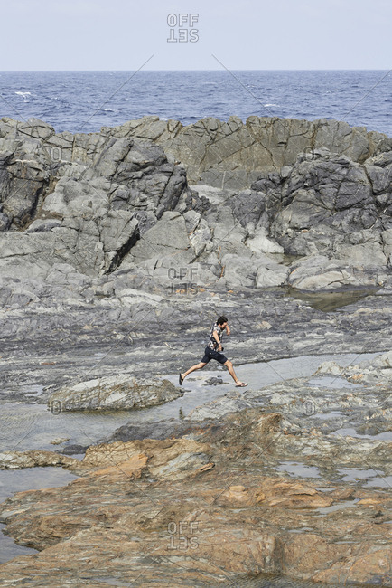 Young brunette man jumping between rocks in rugged landscape against mediterranean sea.