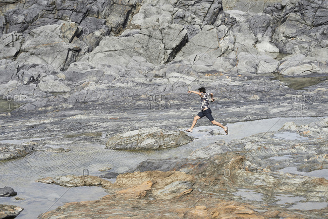 Wanderlust male jumping between rocks in solitude against rugged lunar landscape.
