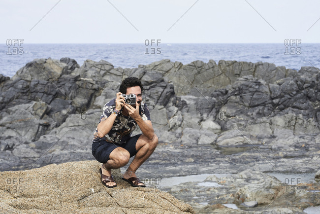 Attractive brunette male taking pictures with film camera against lunar landscape.