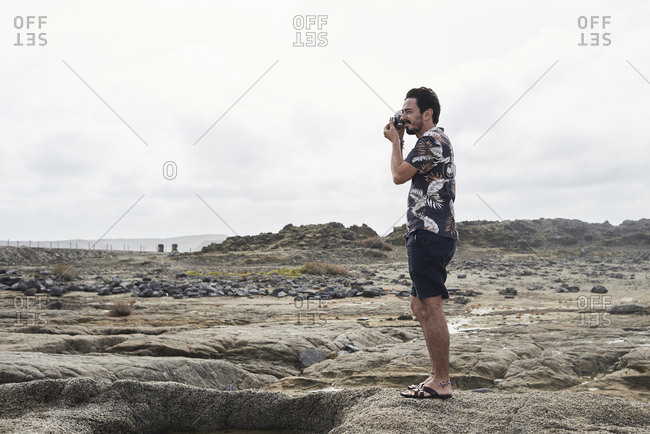 Attractive brunette male taking pictures with film camera against lunar landscape. Cloudy.