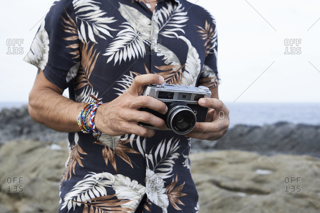 Close up shot of male hands holding classic film camera while traveling around.