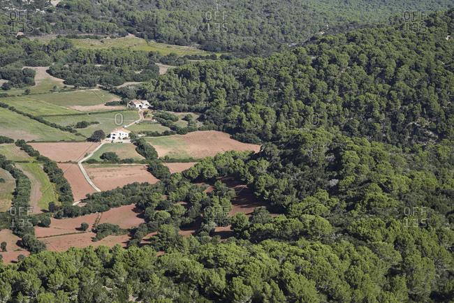 Aerial view of countryside meadow and farmhouse surrounded by forest.