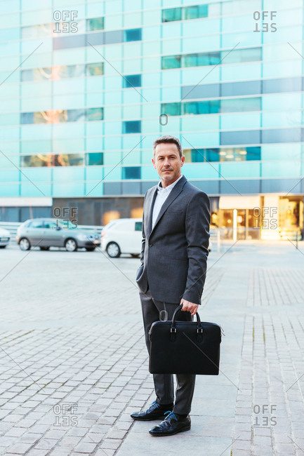Mature businessman wearing an elegant suit holding a briefcase in the city.