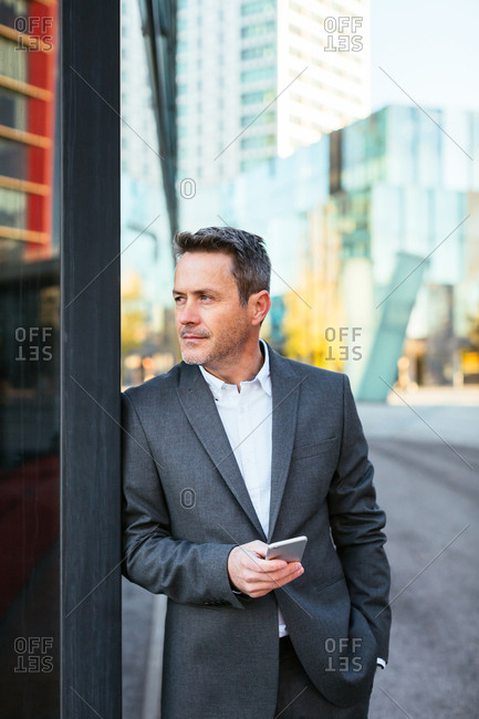 Mature businessman holding phone in the city.