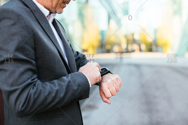 Anonymous businessman looking his wristwatch in the city.