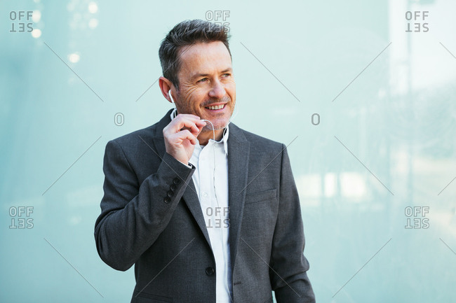 Mature businessman talking on phone in the city.