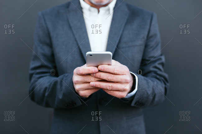 Anonymous businessman using his phone in the city.