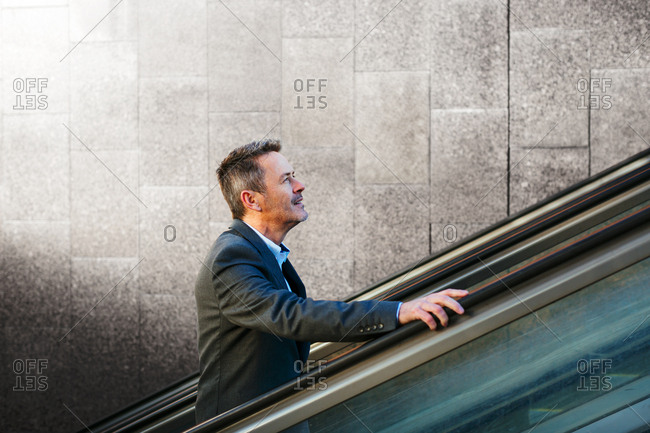 Side view of mature businessman taking the escalator in the subway.