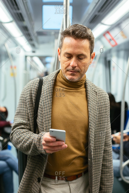 Mature businessman using his phone in the subway.