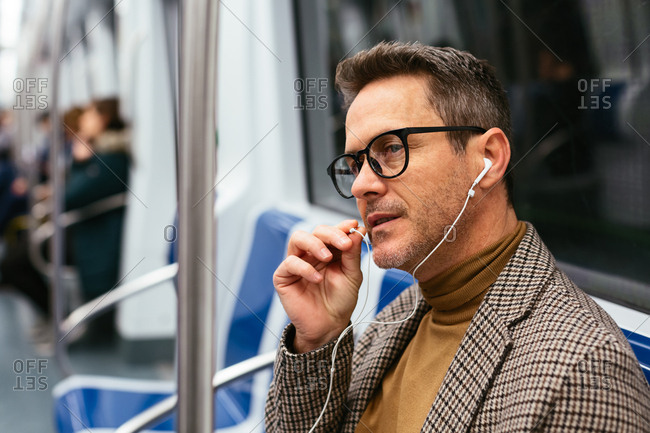 Mature businessman talking with earphones in the subway.