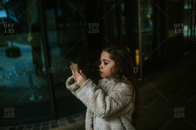 Little girl taking a picture with her phone