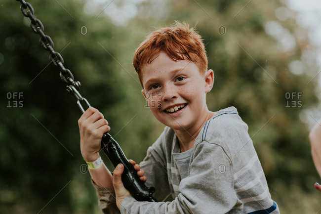 Portrait of a smiling red-haired boy with freckles playing on a tire swing