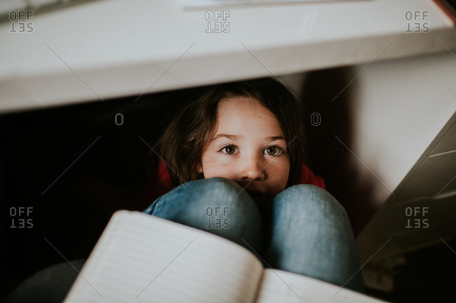 Girl hiding under a desk and looking up