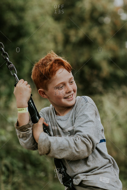 Smiling red-haired boy playing on a tire swing