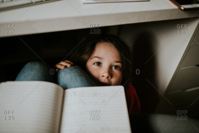 Girl hiding under a desk