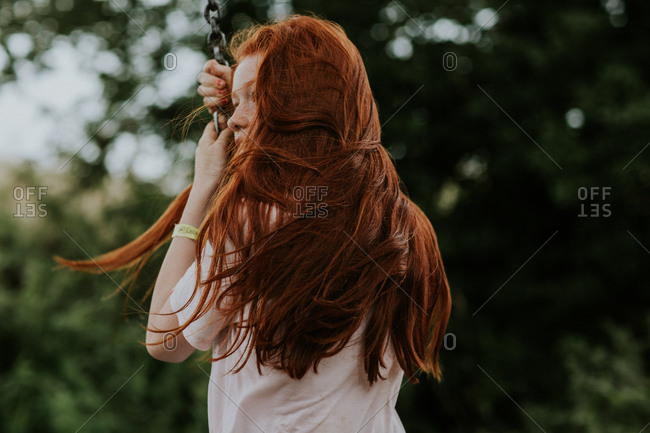 Teenage girl with long red hair playing on a tire swing