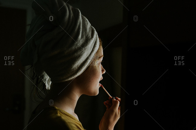 Portrait of a girl with a towel wrapped around her head applying lip gloss
