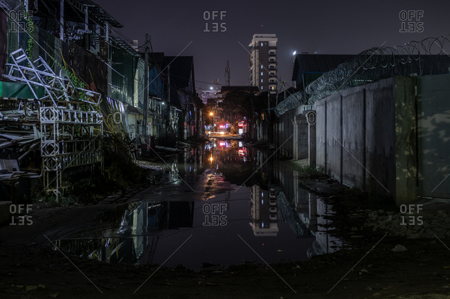 Phnom Penh, Cambodia - December 2, 2018: Buildings and barbed wire reflected in a puddle on the street in the dark of night