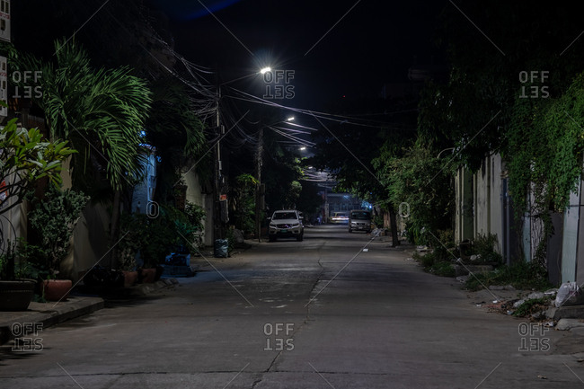 Phnom Penh, Cambodia - December 2, 2018: Cars parked along a narrow street through a neighborhood at night